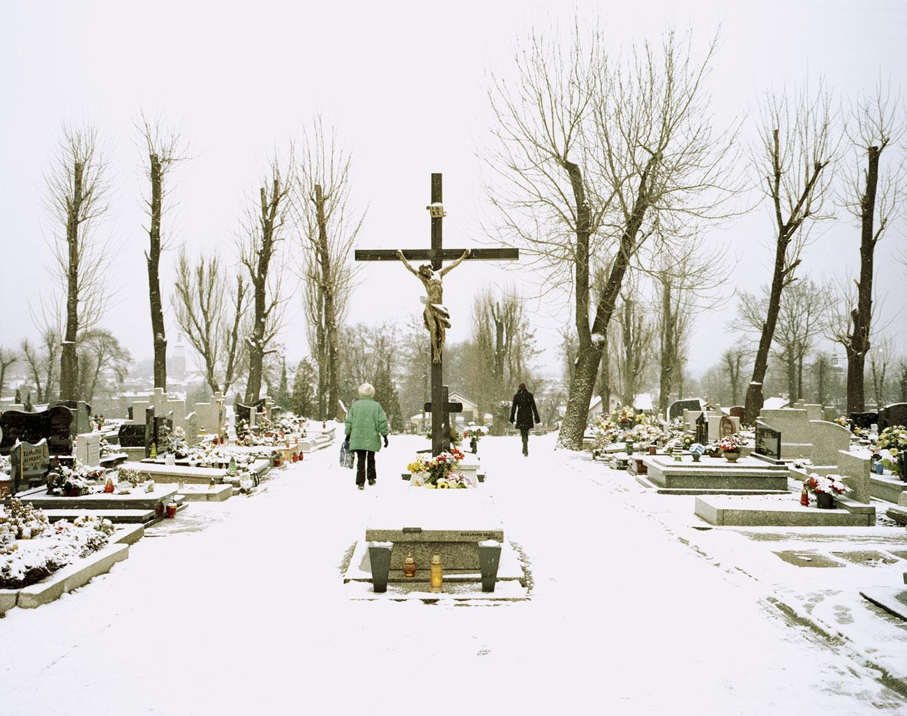 Fotografie eines verschneiten Friedhofs. Zwei Personen bahnen sich ihren Weg durch den Schnee. Auf den Gräbern ist bunter Blumenschmuck zu erkennen. In der Mitte steht ein großes Kreuz mit Christus-Figur.